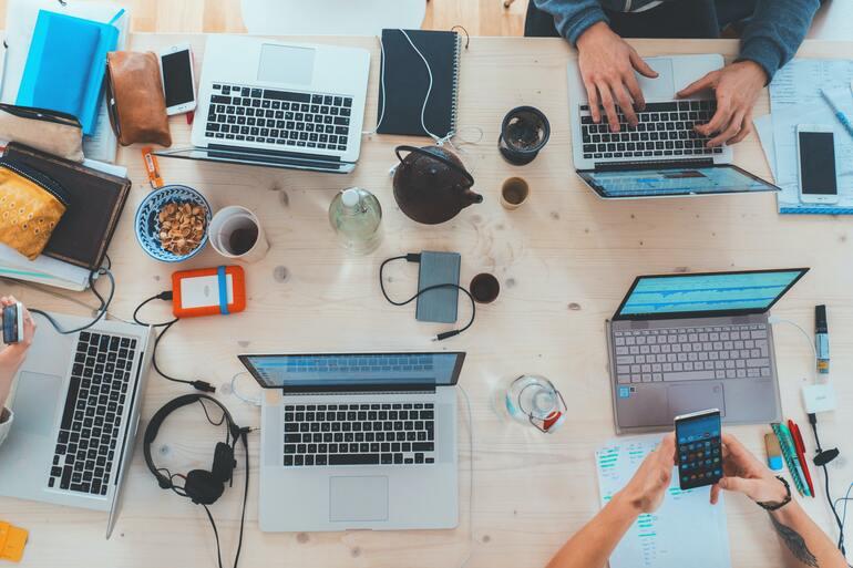 Auf dem Bild ist ein grosser Tisch mit mehreren Laptops zu sehen. Die Abbildung zeigt einen digitalisierten Arbeitsplatz.