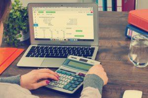 Eine Frau Sitz mit ihrem Laptop am Schreibtisch und rechnet mit dem Taschenrechner etwas nach.