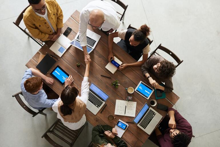 Eine Gruppe von Menschen sitzt an einem Tisch mit Laptops.